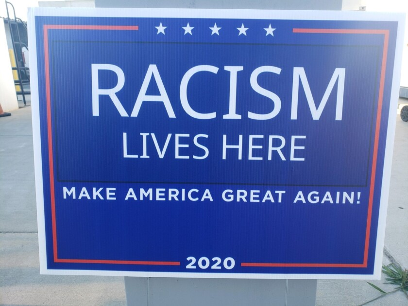 """A lawn sign reads: """"Racism lives here. Make America great again!"""""""