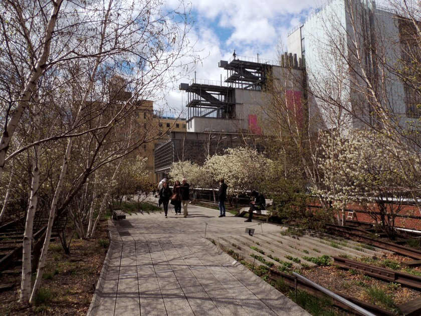 The cantilevered Whitney Museum of American Art appears in the distance overlooking High Line park.