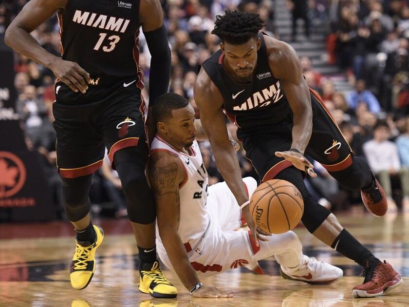 Miami Heat forward Jimmy Butler (22) drives past Toronto Raptors guard Norman Powell during the second half of an NBA basketball game Tuesday, Dec. 3, 2019, in Toronto. (Nathan Denette/The Canadian Press via AP)