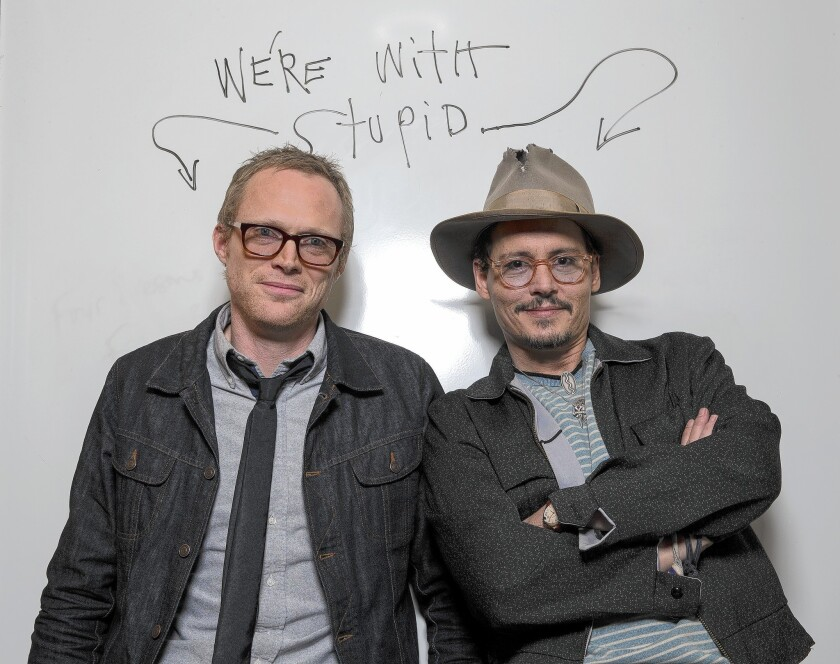 "Johnny Depp, right, poses with Paul Bettany after writing ""we're with stupud"" on a whiteboard at the Four Seasons Hotel while promoting the movie ""Transcendence."""