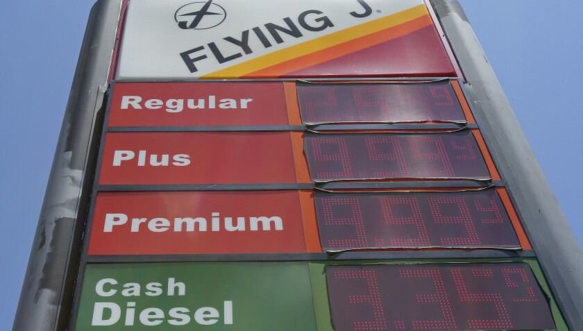 FILE- This June 14, 2018, file photo shows signage and gas prices for regular and diesel at Flying J