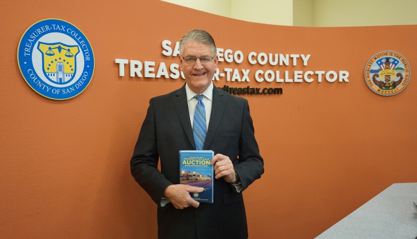 Treasurer-Tax Collector Dan McAllister poses with an old real property auction book. His office is moving auctions for real estate with unpaid property taxes online, making the books obsolete.