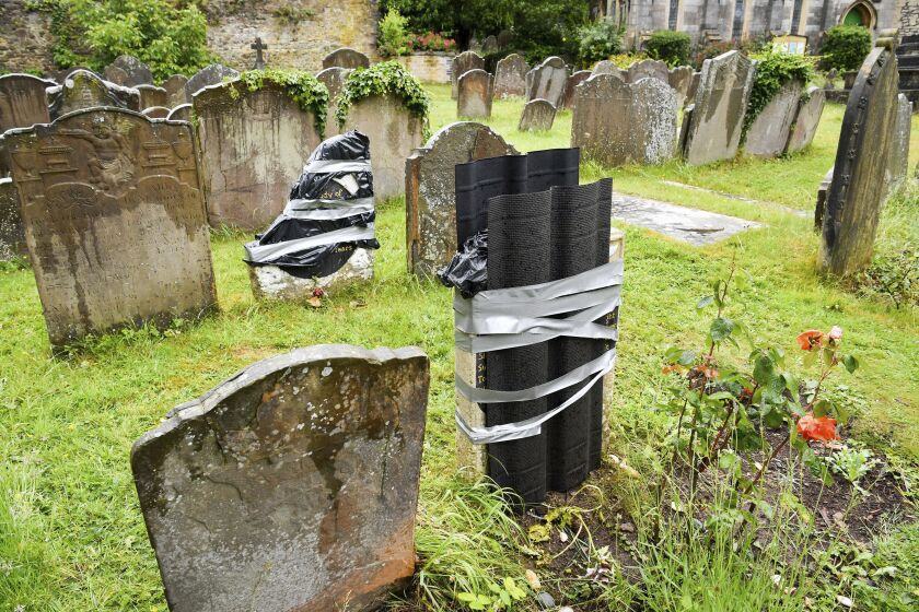 "The damaged headstone and footstone on the grave of an enslaved African man, in St Mary's churchyard, in Bristol, England, Thursday June 18, 2020, which have been vandalised in an apparent ""retaliation attack"" following the toppling of a statue of slave trader Edward Colston during anti-racist protests held in the wake of the killing of George Floyd in the US. The Grade II-listed, brightly painted memorial to Scipio Africanus have been smashed and a message was scrawled in chalk on flagstones nearby. (Ben Birchall/PA via AP)"