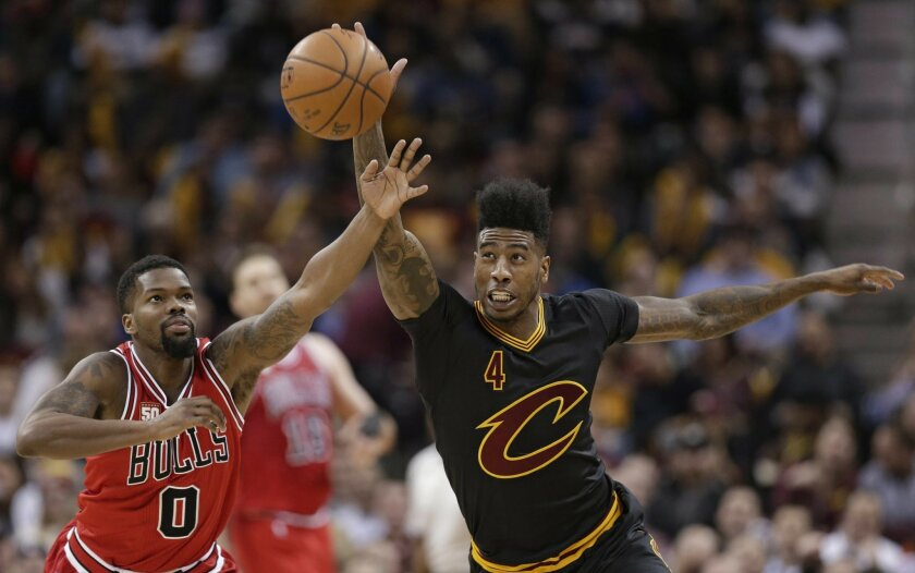 Cleveland Cavaliers' Iman Shumpert (4) and Chicago Bulls Aaron Brooks (0) battle for a loose ball in the second half of an NBA basketball game Thursday, Feb. 18, 2016, in Cleveland. The Cavaliers won 106-95. (AP Photo/Tony Dejak)