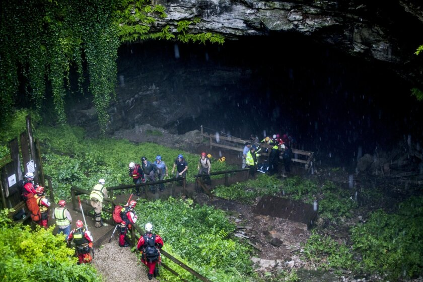 Rescued people walk out of the entrance to Hidden River Cave after officials said over a dozen people who exploring the cave were trapped by rising water Thursday, May 26, 2016, in Horse Cave, Ky. The group waded through neck-deep water to get out, authorities said Thursday. (Austin Anthony/Daily N