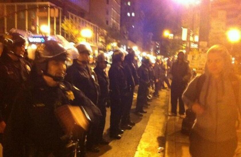 Officers respond to a tense protest in Oakland by forming a line with visors on, pushing protesters away from curb.