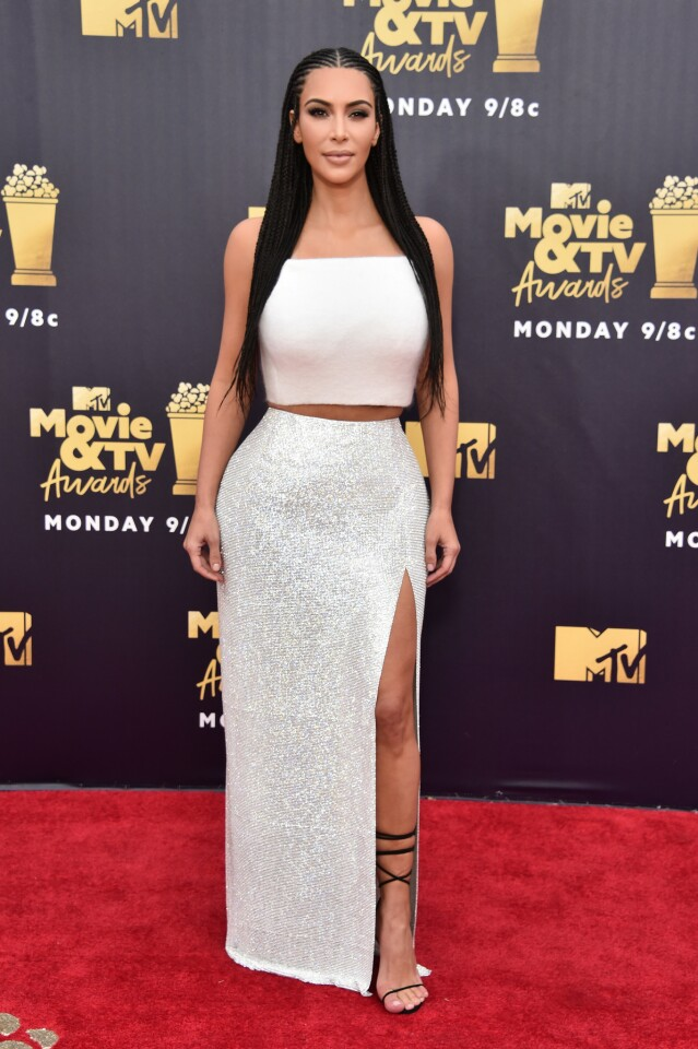 Kim Kardashian flaunted her famous curves in a whit crop top and shimmering skirt for the 2018 MTV Movie And TV Awards at Barker Hangar on June 16, 2018 in Santa Monica, California.