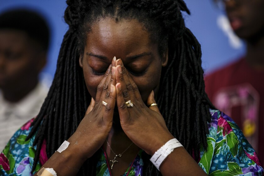 Shetamia Taylor listens during a news conference July 10, as her sons tell reporters of the night when a gunman killed five police officers and wounded seven others, including Taylor.