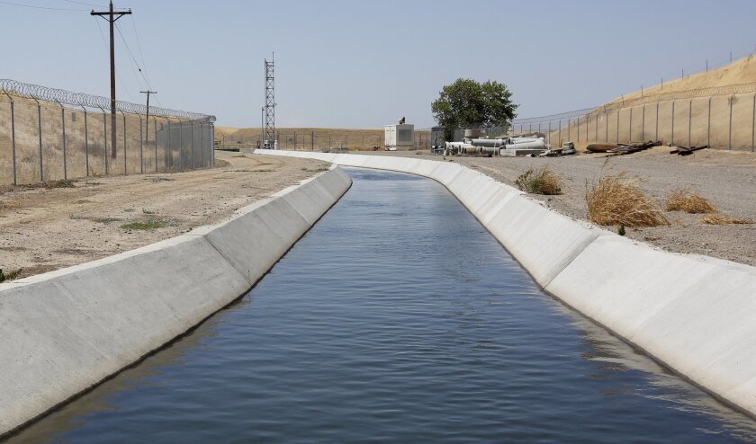 FILE - In this Tuesday, July 21, 2015 file photo, water flows down a diversion canal operated by the Byron-Bethany Irrigation District, that is drawn out of a channel leading to to the William O. Banks pumping plant, near Byron, Calif. Water regulators have recommended dismissing a historic $1.4 mi