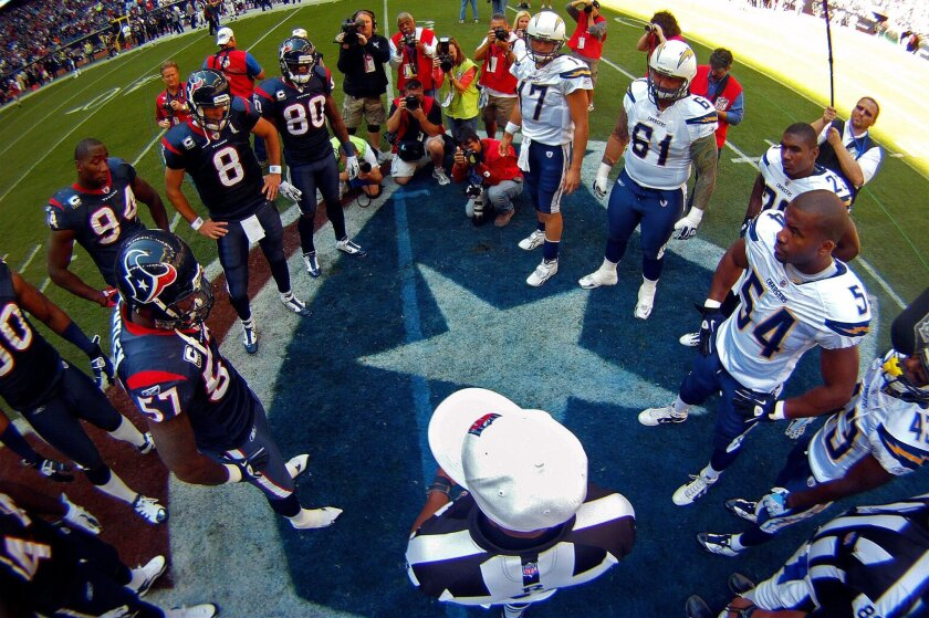 Referee Mike Carey does the coin toss at the start of the Chargers-Texans game at Reliant Stadium on Sunday, Nov. 7, 2010.