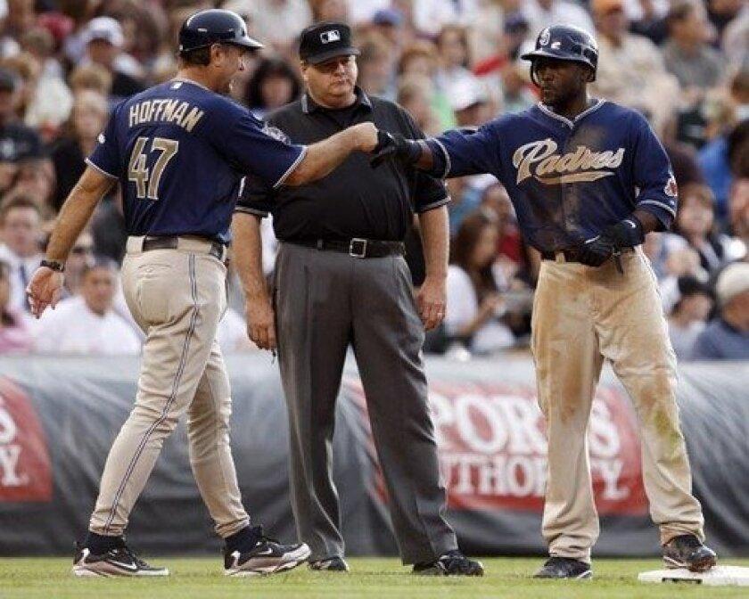 Padres third base coach Glenn Hoffman, left, congratulates Tony Gwynn Jr. after his RBI-triple against the Rockies in the fourth inning Saturday.
