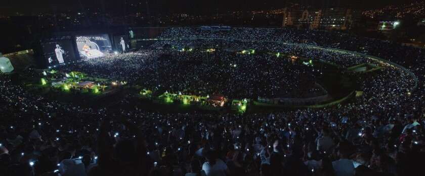 A stadium is packed with people holding up their cellphone lights.