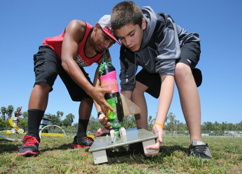 Bear Valley Middle School students Devin Celestine (left) and Tyler Socin prepare their rocket for launch at the school.