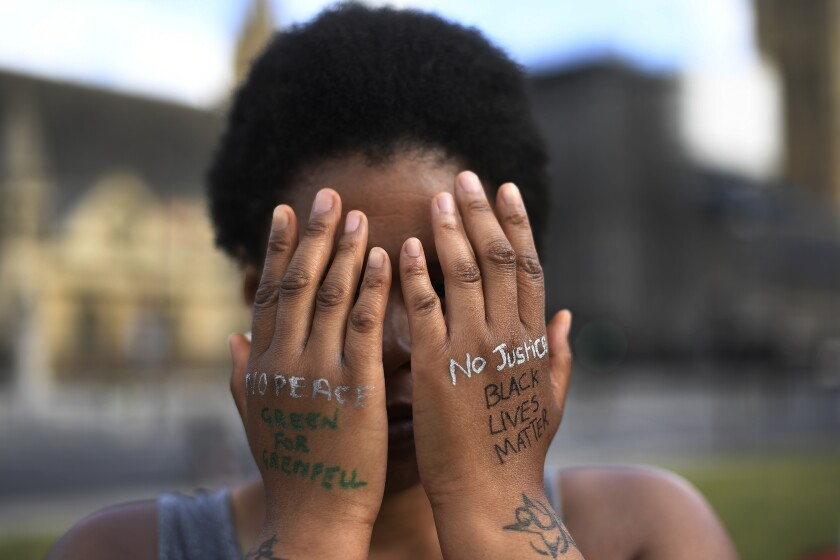 A woman symbolically covers her eyes as she participates in a Black Lives Matter protest