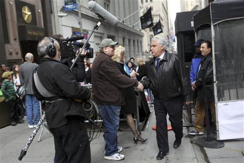 """FILE - In this March 27, 2009 file photo, filmmaker Michael Moore, center, tries to speak to traders outside the New York Stock Exchange for his latest documentary looking at the consequences of corporate profiteering called """"Capitalism: A Love Story."""" (AP Photo/Mary Altaffer)"""