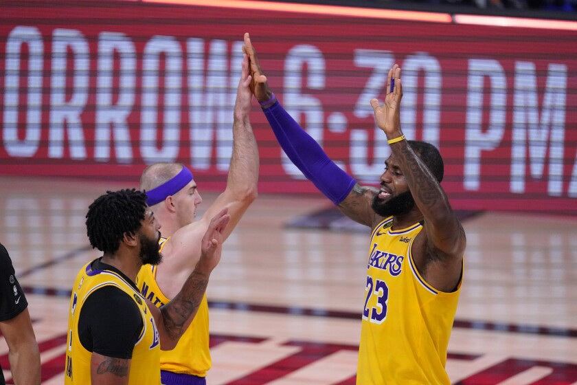 LeBron James (23) celebrates with Anthony Davis, left, and Alex Caruso after beating the Rockets on  Sept. 10.