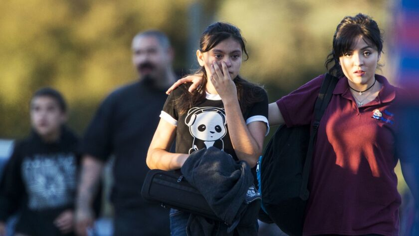 Parents evacuate their children after Slauson Middle School was placed on lockdown during a shooting at the intersection of Orange Avenue and Fourth Street in Azusa.