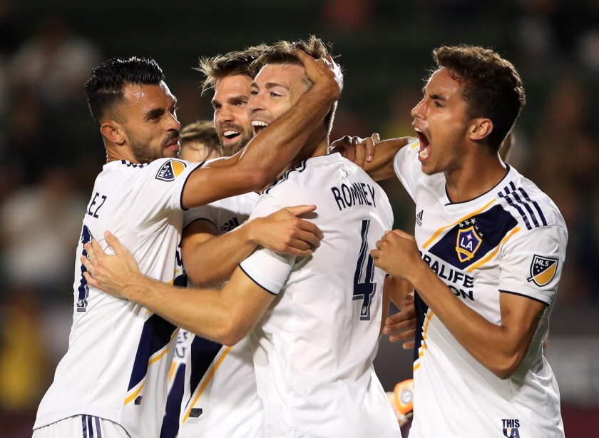 Galaxy's Dave Romney (4) is congratulated after scoring a goal by Ethan Zubak (29) , Efrain Alvarez (26) and Emil Cuello (27) during the second half of the quarterfinal match against Tijuana of the 2019 Leagues Cup at Dignity Health Sports Park on Tuesday.