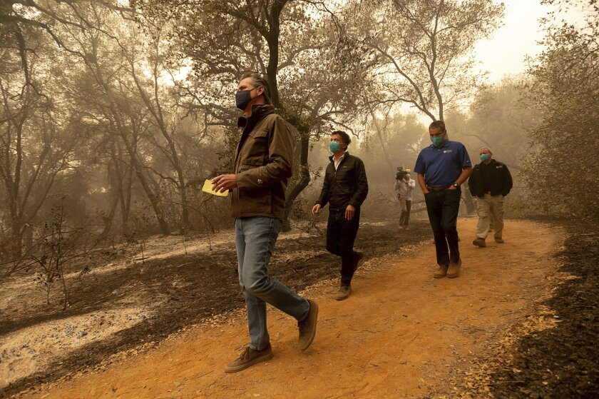 Gov. Gavin Newsom takes notes as he tours the North Complex fire zone.