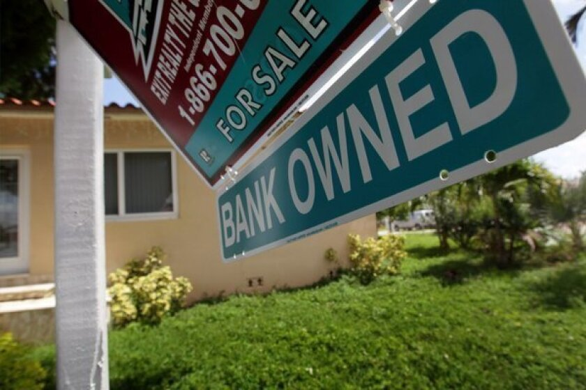 """A """"Bank Owned"""" sign in front of a foreclosed home in Miami in September."""