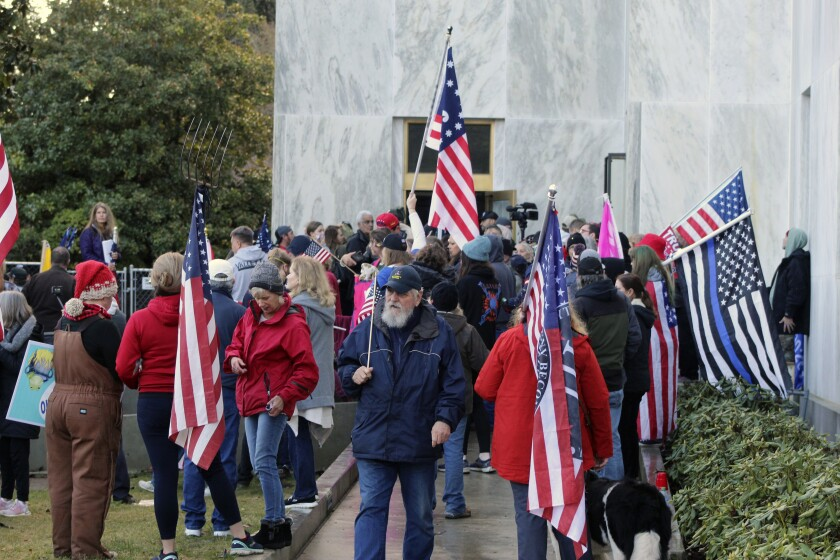 FILE - In this Dec. 21, 2020, file photo, pro-Trump and anti-mask demonstrators hold a rally outside the Oregon State Capitol as legislators meet for an emergency session in Salem, Ore. Oregon House Speaker Tina Kotek wants to expel a lawmaker who allowed violent protesters into the Oregon State Capitol that day. (AP Photo/Andrew Selsky, File)