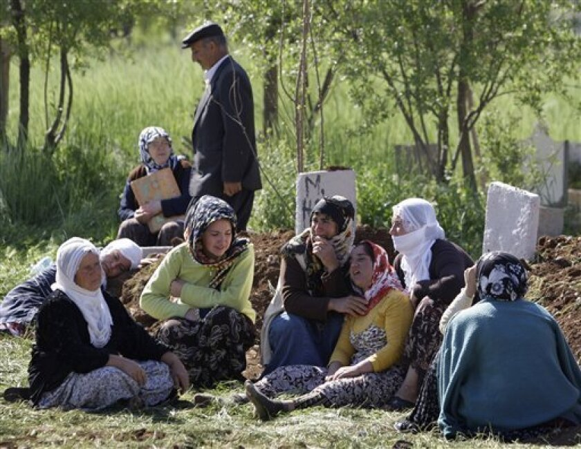 Women mourn near the graves of their family members in the village of Bilge, near the city of Mardin in southeastern Turkey, Wednesday, May 6, 2009. Masked assailants with automatic weapons attacked a celebration Monday night, killing 44 people and injuring six others in what appeared to be the result of a family feud, according to Turkish authorities. Hasan Duruer, the governor of Mardin province, said Wednesday a court has charged eight suspects accused of killing 44 people in an assault on an engagement ceremony in Bilge.(AP Photo/Ibrahim Usta)
