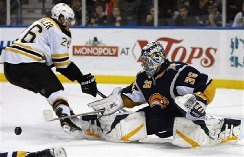 Buffalo Sabres goalie Ryan Miller makes a save under pressure from Boston Bruins' Blake Wheeler (26) during the second period of an NHL hockey game in Buffalo, N.Y., Tuesday, Feb. 9, 2010. (AP Photo/David Duprey)