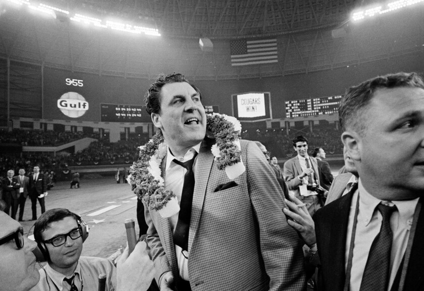 Guy V. Lewis, University of Houston basketball coach, wears a garland of flowers after the Houston C
