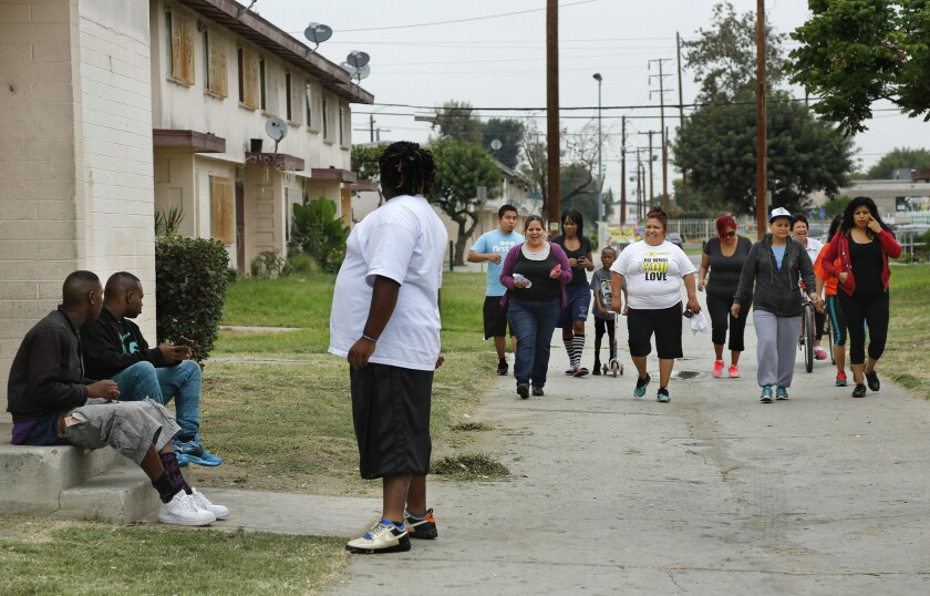 Community members in the Jordan Downs Housing Development in Watts, including Amada Valle, 58, in white shirt, Vice President of the Jordan Downs Resident Advisory Council, head out on their weekly Friday morning walk around the development on July 31.