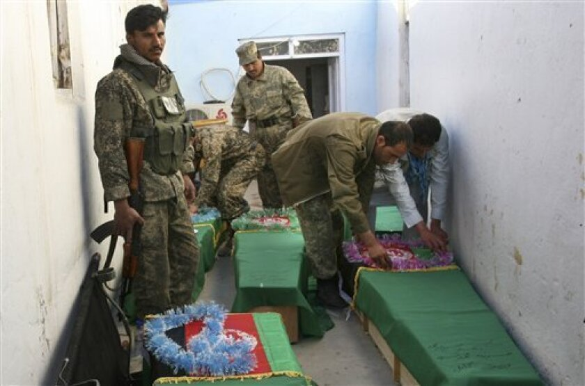 Afghan Army soldiers prepare the coffins for their killed comrades in the morgue of the main hospital in Ghazni, Afghanistan, Wednesday, April 17, 2013. A roadside bomb killed the five soldiers who were part of a government security force guarding a convoy of trucks in Ghazni's Qarabagh district. R