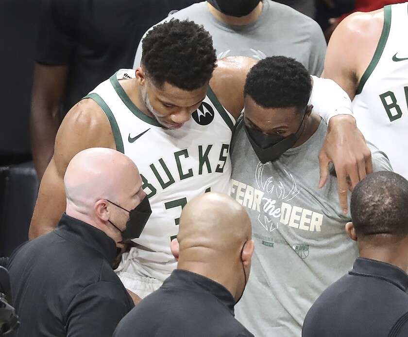 Milwaukee Bucks forward Giannis Antetokounmpo is helped up by his brother Thanasis Antetokounmpo (right), who also plays for the team, after he hyperextended his left knee on this play hitting the floor after rising to challenge a slam by Atlanta Hawks center Clint Capela on a lob pass by Lou Williams with 7:14 left in the third quarter of game 4 in the NBA Eastern Conference Finals on Tuesday, June 29, 2021, in Atlanta. (Curtis Compton/Atlanta Journal-Constitution via AP)