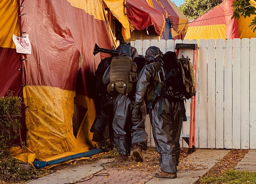 Los Angeles County sheriff's deputies enter a tented home in Whittier, where a man was found dead Tuesday.