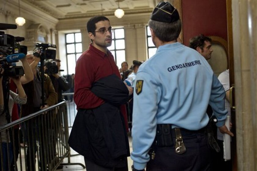 French nuclear physicist Adlene Hicheur's brother Halim Hicheur talks to a police officer at the Paris courthouse, in Paris, Thursday March 29, 2012 where Adlene Hicheur goes on trial charged with criminal association as part of a terrorist enterprise. In a series of emails the nuclear physicist railed about a need to punish Western governments for allegedly anti-Muslim wars in Iraq and Afghanistan _ and conferred with an alleged al-Qaida in the Islamic Maghreb contact about possible assassination or bombing plots. Hicheur has been jailed since he was arrested in on Oct 2009 at his parents' home in southeastern France. If found guilty, Hicheur could be sentenced to 10 years in prison. (AP Photo/Thibault Camus)