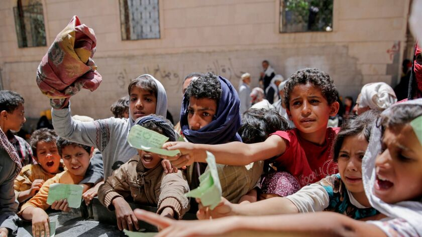 FILE - In this April 13, 2017, file photo, Yemenis present documents in order to receive food ration