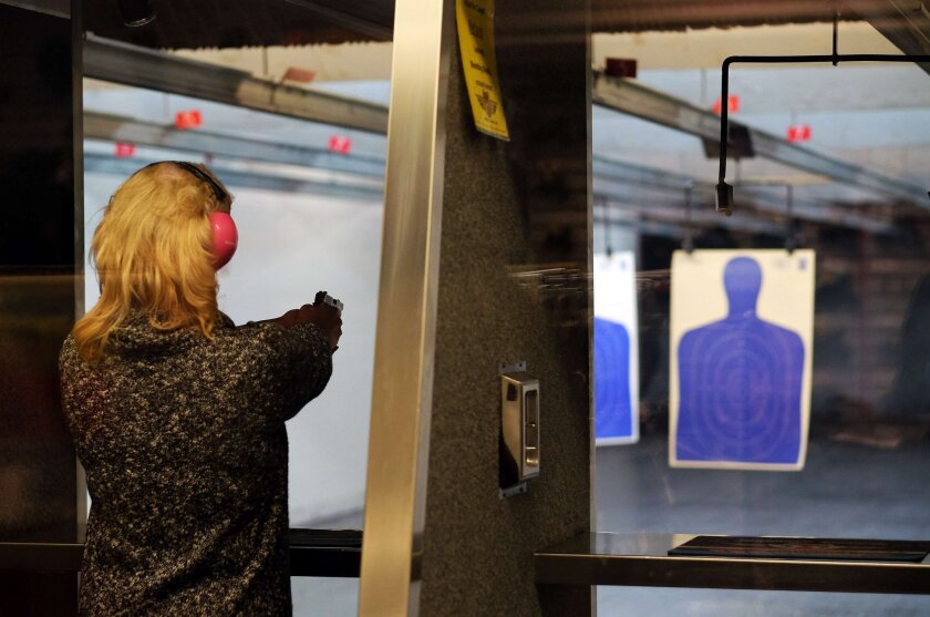 A woman fires a gun at the Ultimate Defense Firing Range and Training Center in St. Peters, Mo. A Pew survey finds growing support for gun rights.
