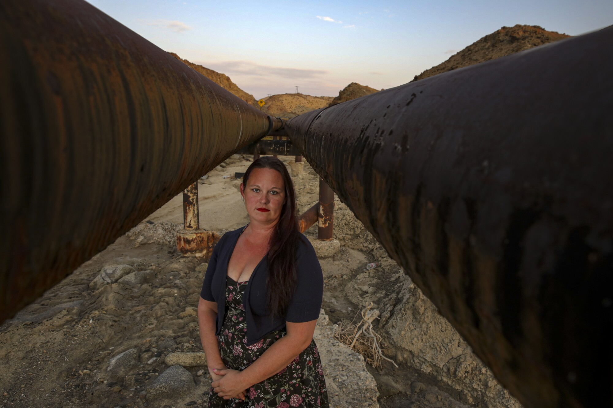 A woman stands between two large elevated water pipes