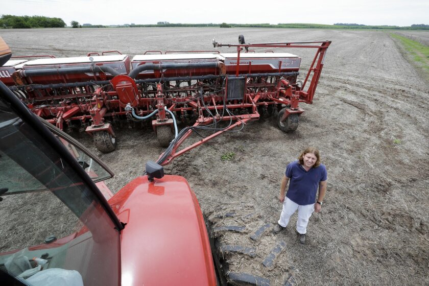 In this Nov. 11, 2015 photo, businessman Marcelo Cervigni poses for a photo next to a tractor, before planting soy, on his land in Capilla del Senor, Buenos Aires' province, Argentina. For sectors ranging from agricultural to banking, there is a lot at stake for Latin America's third largest economy in Sunday's presidential election. (AP Photo/Victor R. Caivano)