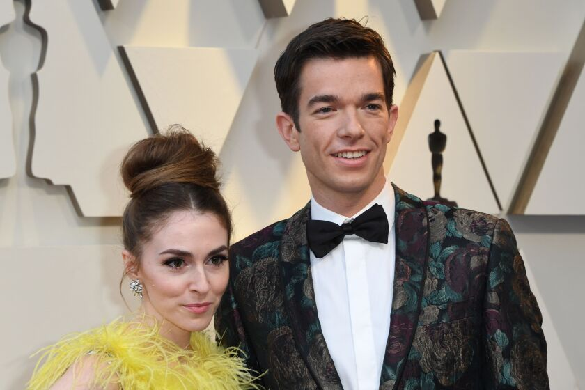 John Mulaney and Anna Marie Tendler taking a photo together at the Oscars.