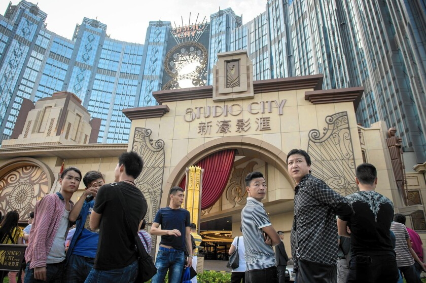 People wait outside the Studio City casino-resort ahead of its opening in Macau. Casino operator Melco Crown Entertainment built its latest resort as Macau scrambles to attract mass-market visitors amid falling gambling revenue.
