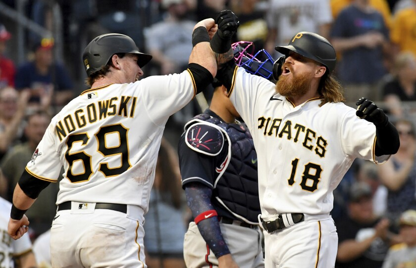 Pittsburgh Pirates' John Nogowski, left, congratulates Ben Gamel after Gamel hit a two-run home run against the Atlanta Braves in the fourth inning of a baseball game Monday, July 5, 2021, in Pittsburgh. (Matt Freed/Pittsburgh Post-Gazette via AP)