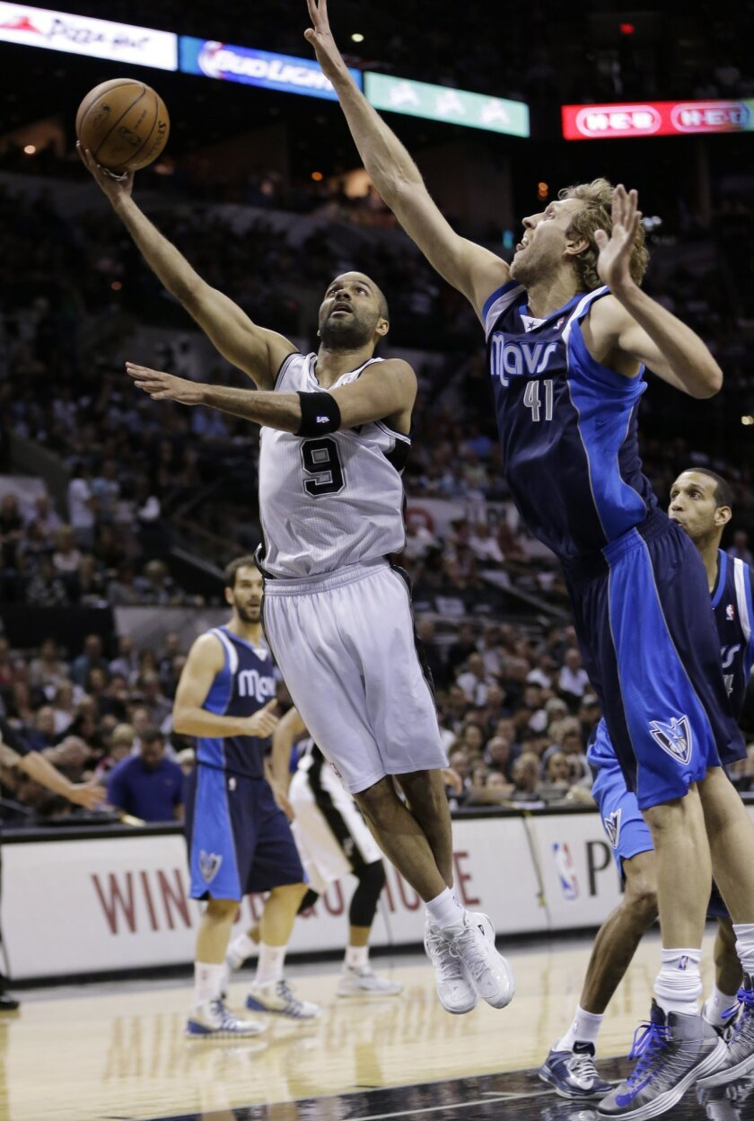 San Antonio Spurs' Tony Parker (9), of France, shoots around Dallas Mavericks' Dirk Nowitzki (41), of Germany, during the first half of Game 5 of the opening-round NBA basketball playoff series on Wednesday, April 30, 2014, in San Antonio. (AP Photo/Eric Gay)