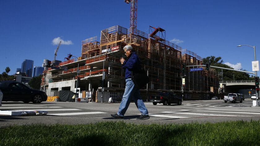 A man walks near a residential project going up at the corner of Cesar Chavez and Broadway near Chinatown on March 18.