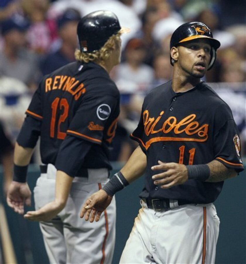 Baltimore Orioles' Robert Andino (11) and Mark Reynolds (12) react after scoring on a seventh-inning single by teammate J.J. Hardy off Tampa Bay Rays starting pitcher David Price during a baseball game on Friday, Sept. 2, 2011, in St. Petersburg, Fla. (AP Photo/Chris O'Meara)