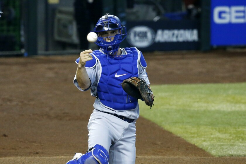 Dodgers catcher Will Smith tosses a ball out of play.