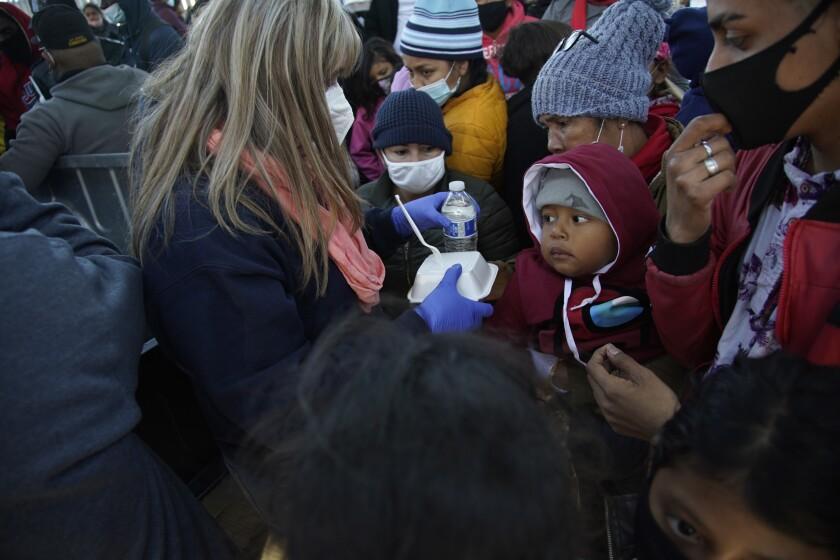 Asylum seekers gather at a border crossing.