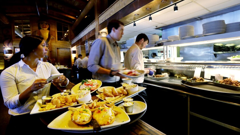 Servers prepare food orders at an Ivar's restaurant in Seattle. In Seattle restaurants the number of