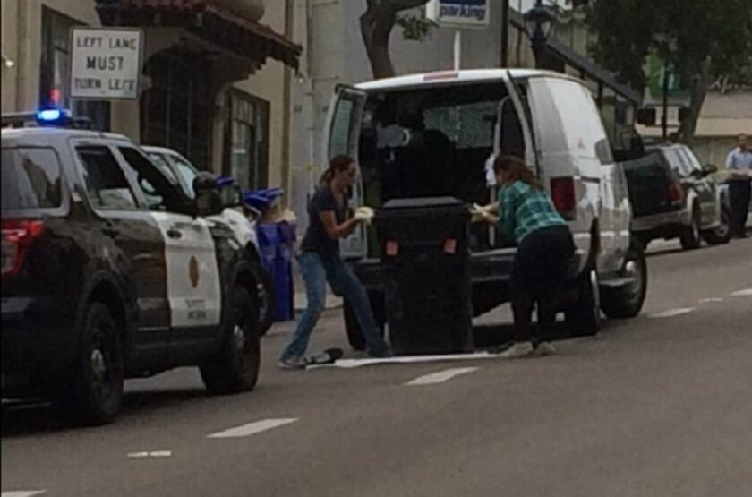 A crew lifted the trash can that contained the suitcase the body was in and put it into a van to later analyze it for evidence.