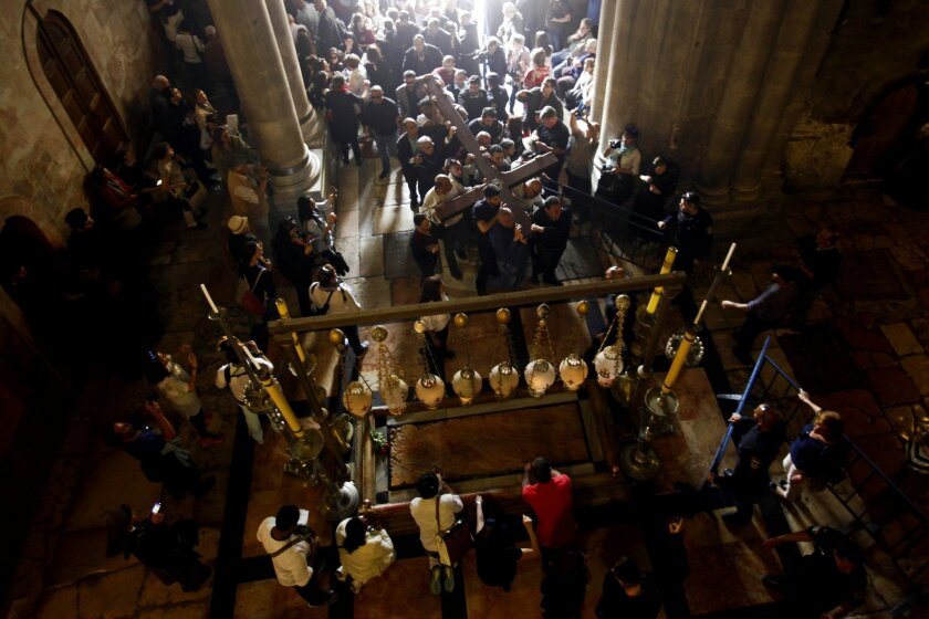 Christian faithful carry a cross into the Church of the Holy Sepulchre in Jerusalem, Friday, March 25, 2016. Catholics and Protestants commemorated the crucifixion of Jesus Christ by following the path in Jerusalem's Old City where, according to tradition, he walked on the way to the cross. (AP Pho