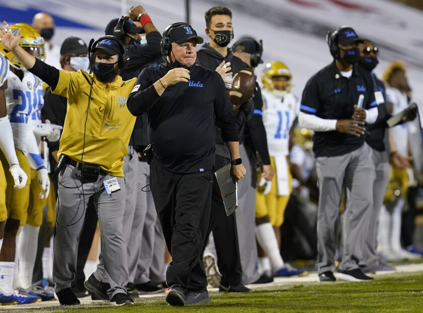 UCLA head football coach Chip Kelly walks along the sideline during a game.