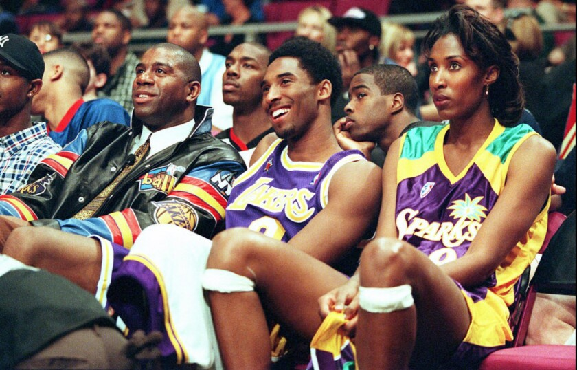 Lakers star Kobe Bryant, center, sits between Magic Johnson, left, and Sparks star Lisa Leslie at an event during the 1998 NBA All-Star Weekend in New York.